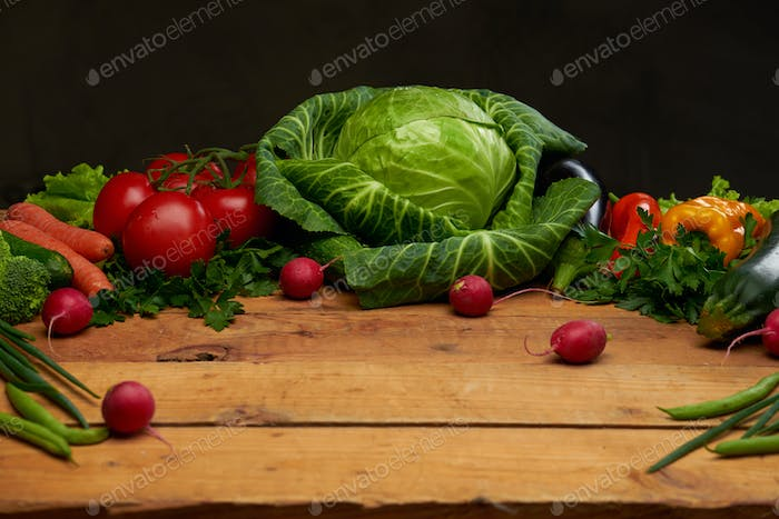Fresh organic vegetables on a wooden boards background, top view.