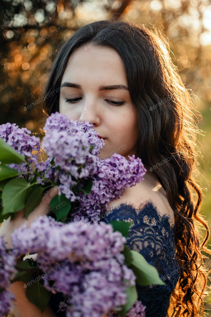 Beautiful Young Brunette Woman with Lilac bouquet. Outdoor photo of beautiful young woman with
