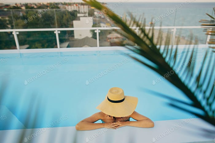 Stylish young woman in hat relaxing in pool under palm leaves and enjoying summer holiday