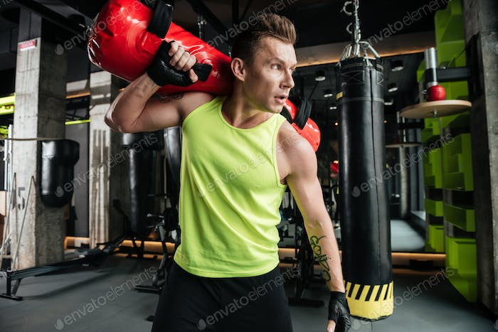 Young serious sportsman make sport exercises in gym