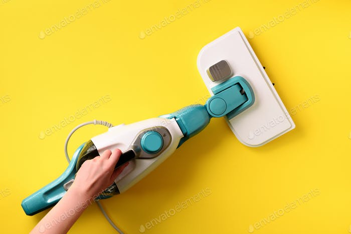 Steam cleaner mop on yellow background. Top view, flat lay. Banner with copy space. Cleaning service