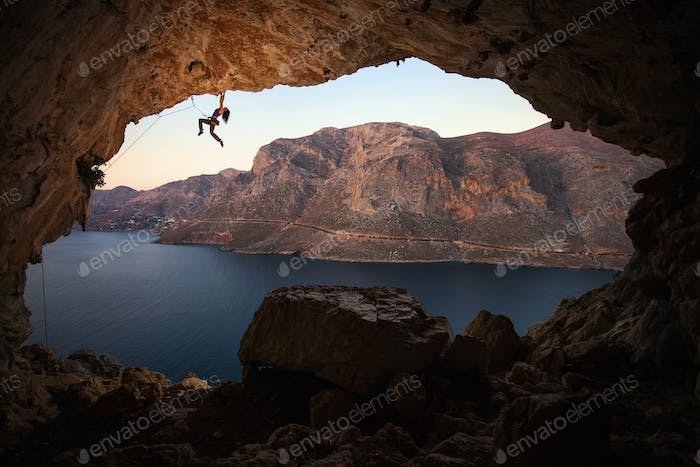 Silhouette of a female rock climber on a cliff in a cave at Kalymnos