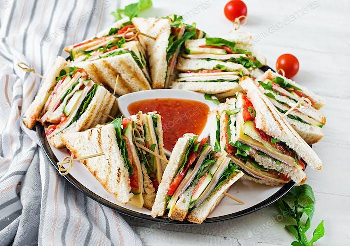 Club-Sandwich mit Schinken, Tomaten, Gurken, Käse und Rucola auf hölzernem Hintergrund.