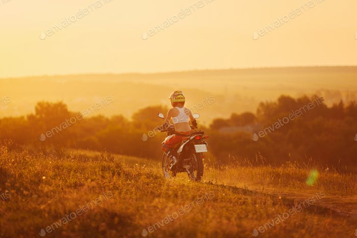 Woman biker in sunset, female motorcycle.