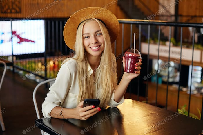 Cheerful attractive blue eyed young blonde lady wearing trendy clothes while sitting