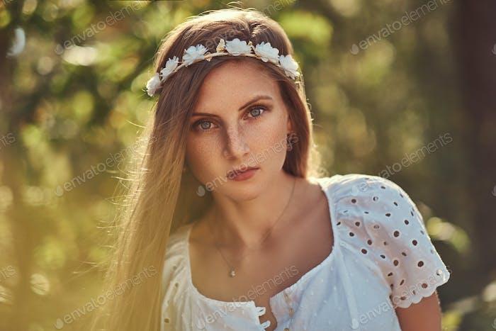 Eine schöne Frau in einem weißen Kleid und weißen Kranz auf Kopf posiert in einem grünen Herbstwald.
