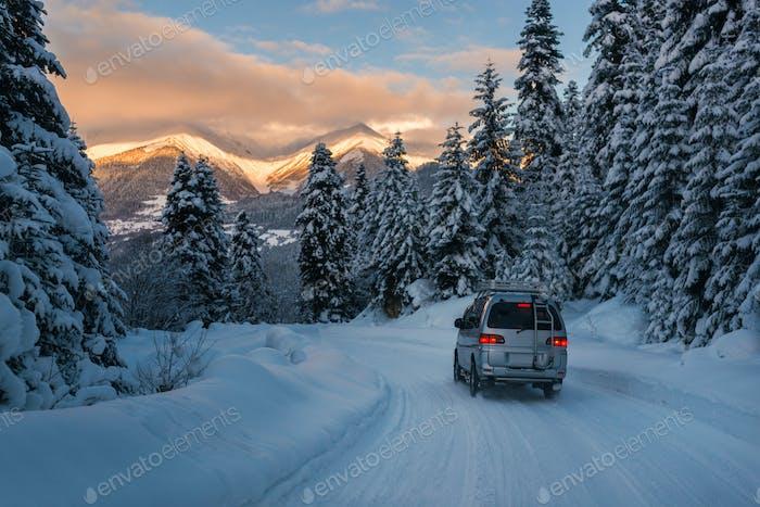 das Auto fährt auf der Pulverschnee-Straße in den Bergen
