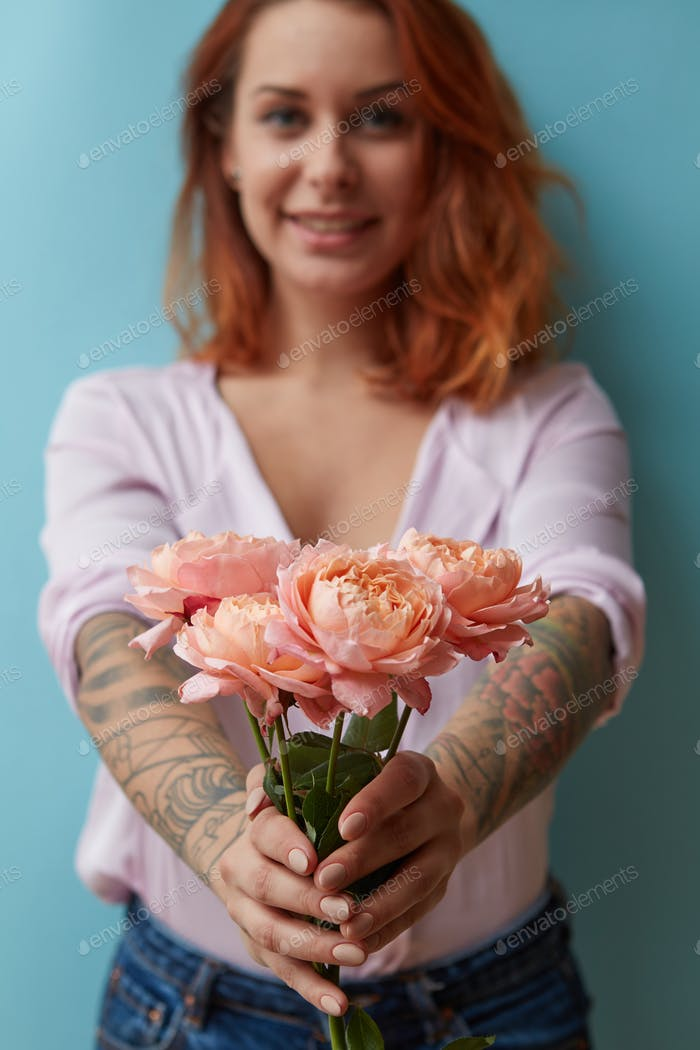 A smiling girl with a tattoo gives a bouquet of pink roses around a blue background with copy space
