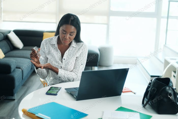African American Woman Using Hand Sanitizer