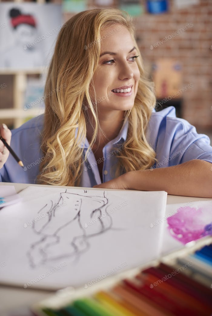 Cheerful woman over her drawings