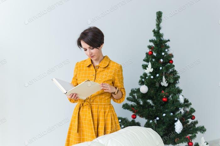 Frau liest Buch vor dem Weihnachtsbaum. Weihnachten, Feiertage