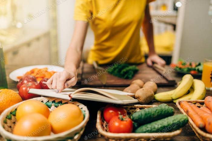 Young woman cooking on recipes, healthy bio food