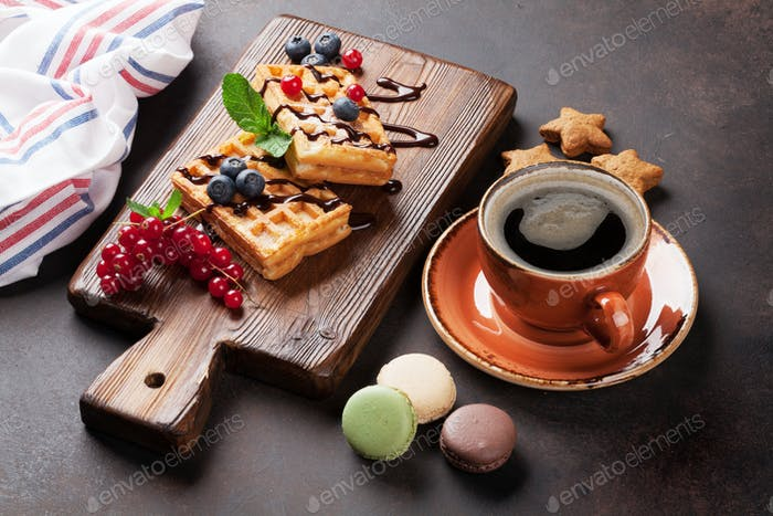 Coffee, sweets and waffles with berries