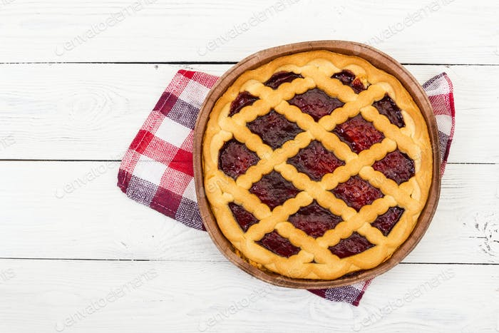 Pie with cherry jam on wooden background.