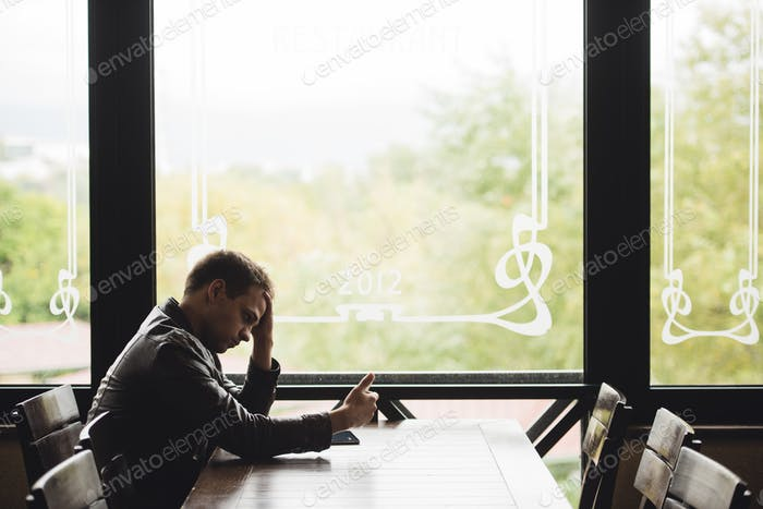 Portrait of tired young businessman typing on cellphone at cafe