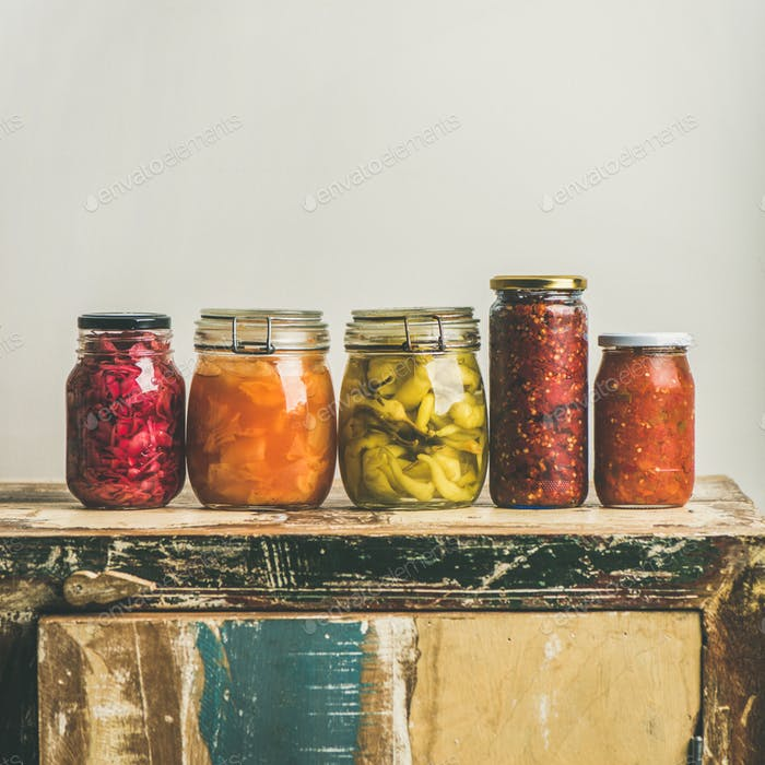 Autumn pickled vegetables in jars placed in line, square crop