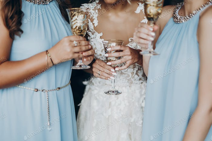 Gorgeous bride and bridesmaids toasting with champagne and having fun in hotel room
