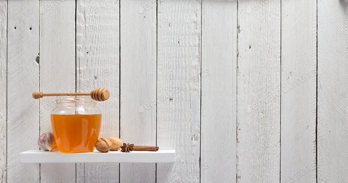 glass jar of honey on wooden shelf