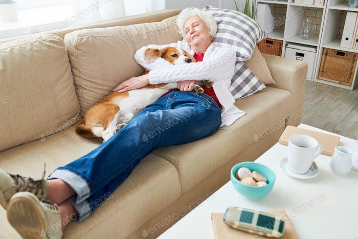 Senior Woman Enjoying Nap with Dog
