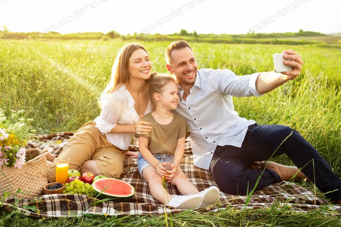 Happy family taking selfie sitting in the countryside