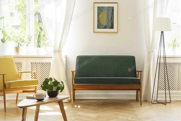 Poster above green bench between lamp and yellow armchair in vin