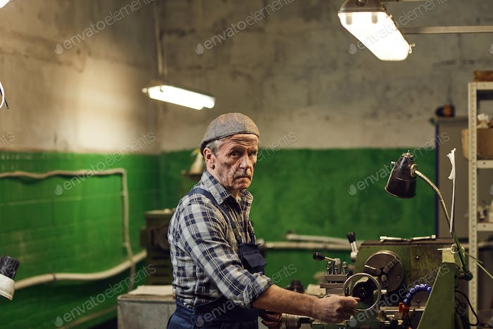 Mature manual worker working on lathe