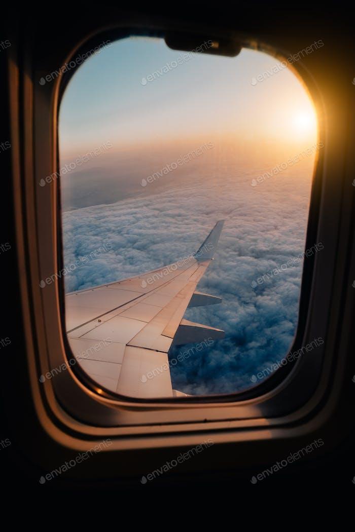 Evening airplane flight in twilight sky. Sunset view in cabin frozen window frame
