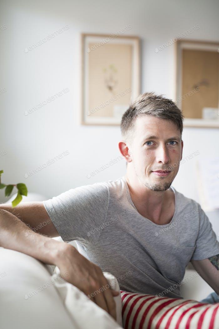 Retrato del hombre adulto medio sentado en el sofá en casa