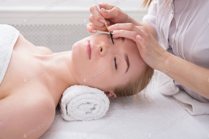 Woman gets eyelashes tinting by beautician at spa