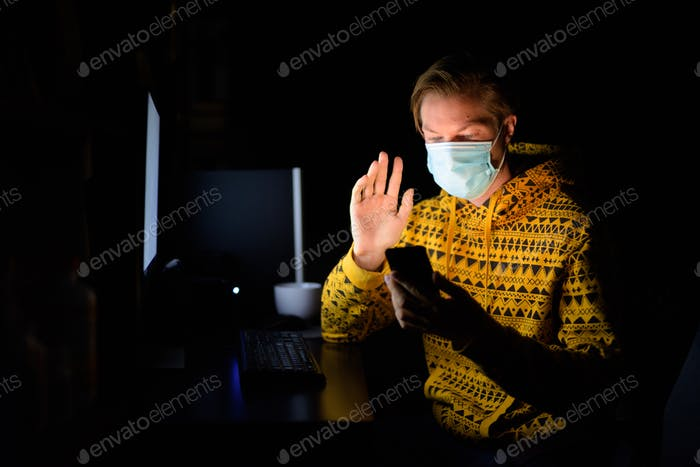 Young man with mask video calling while working from home late at night in the dark
