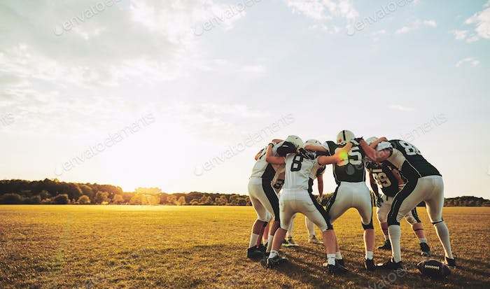 American football players in a huddle during practice