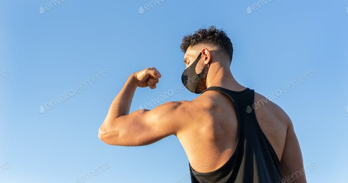 Athletic caucasian man wearing face mask showing his biceps on blue sky background
