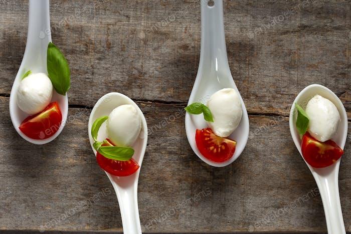 Spoons with mozzarella cheese balls, cherry tomato and basil