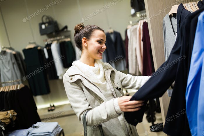 Young attractive woman buying clothes in mall