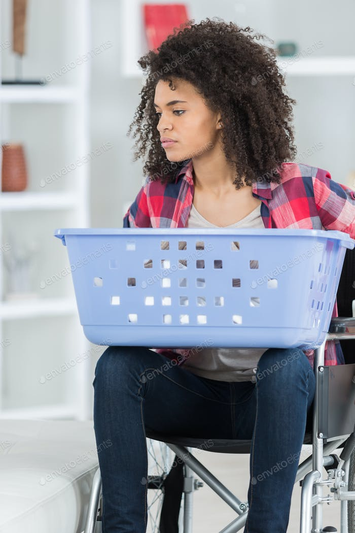 woman on wheelchair carring a basket to do laundry