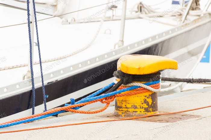 Closeup and detail of yachting, Colorful rope with old mooring bollard in seaport
