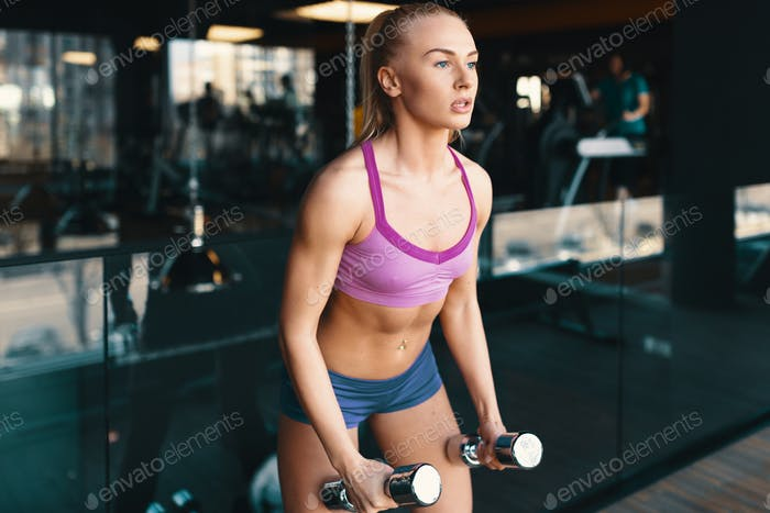 Young Caucasian woman doing exercise with dumbbells while traini