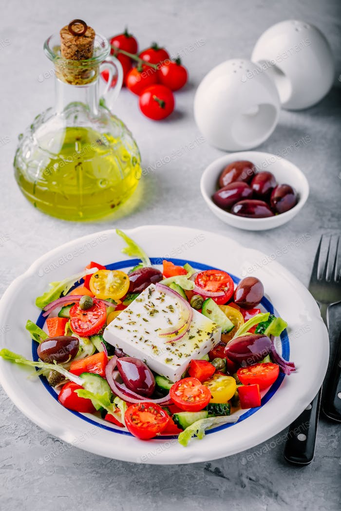 Delicious Greek salad with feta cheese, olives, tomatoes, cucumbers, paprika and red onions.