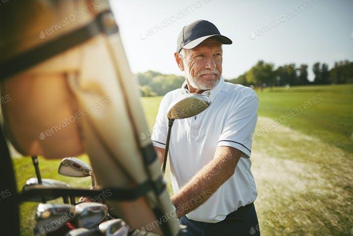 Senior Mann bereit, Golf an einem sonnigen Tag zu spielen