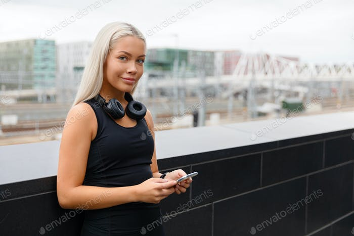 Smiling Fit Female Athlete with Headphones and Smartwatch In the City