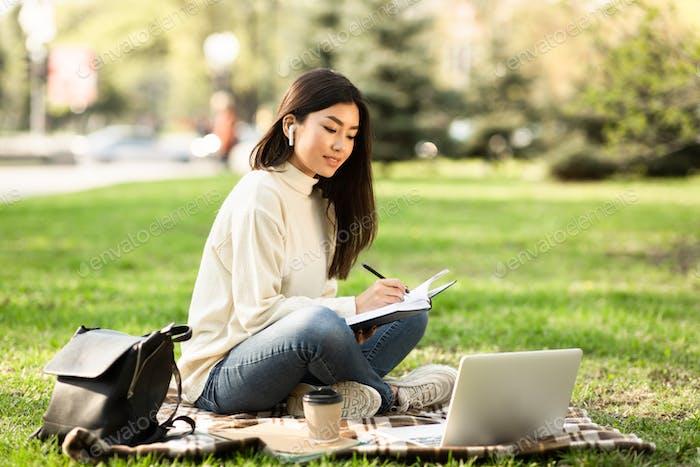 Girl writing in diary, sitting in parkland near university