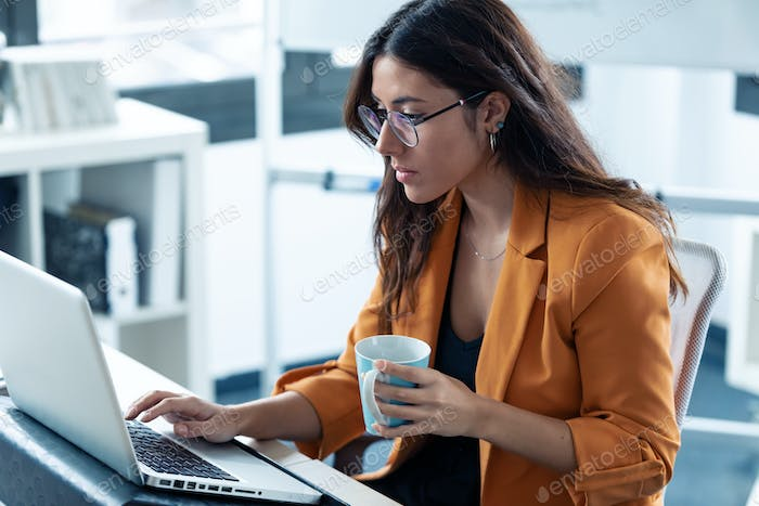Business young woman drinking coffee while working with laptop in the office.