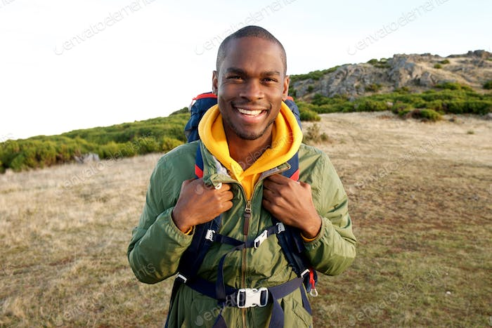 smiling young black man with backpack standing in nature