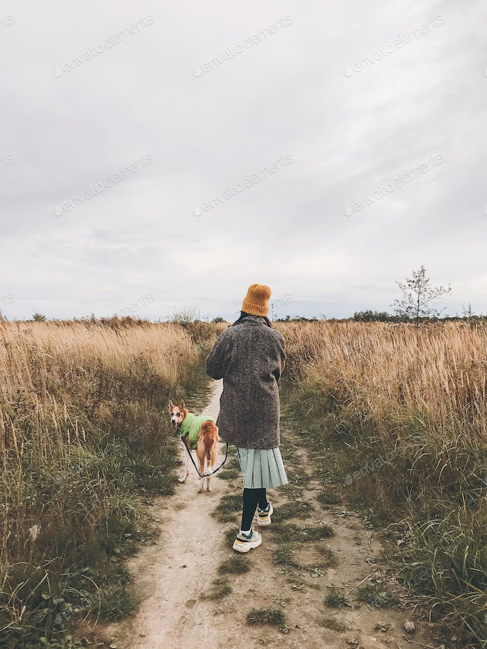 Hipster girl in yellow hat and in coat walking with her golden dog