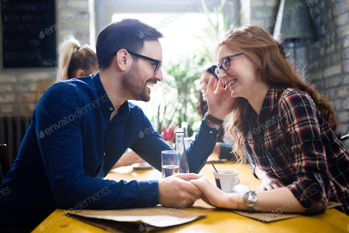 Happy couple flirting and dating in restaurant