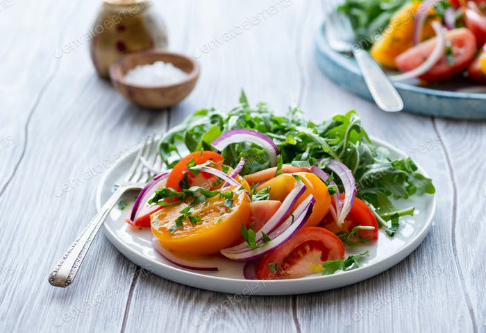 Colorful heirloom tomato salad with arugula