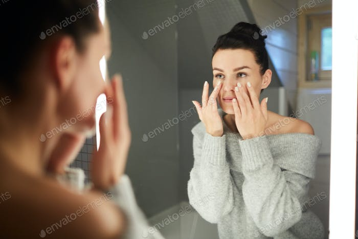 Applying cream on cleaned face