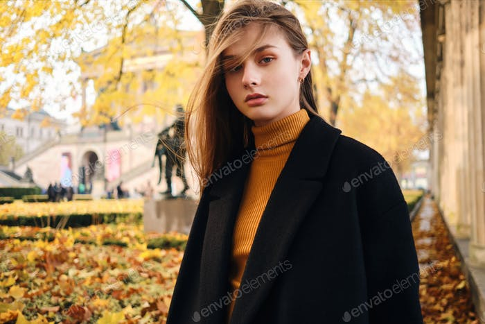 Beautiful stylish girl confidently looking in camera on beautiful autumn city street