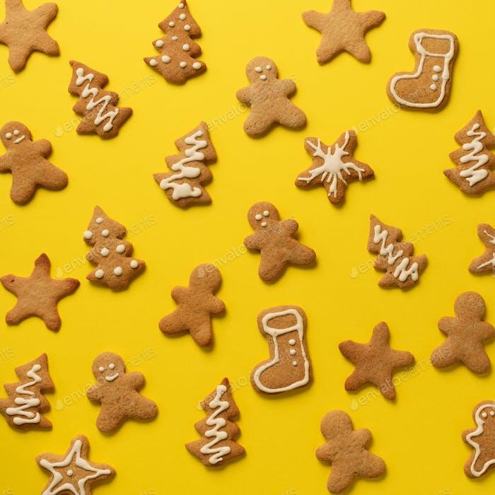 Hausgemachte Weihnachtsplätzchen auf gelbem Hintergrund. Quadratische Ernte. Muster von Lebkuchenmännern, Schneeflocke