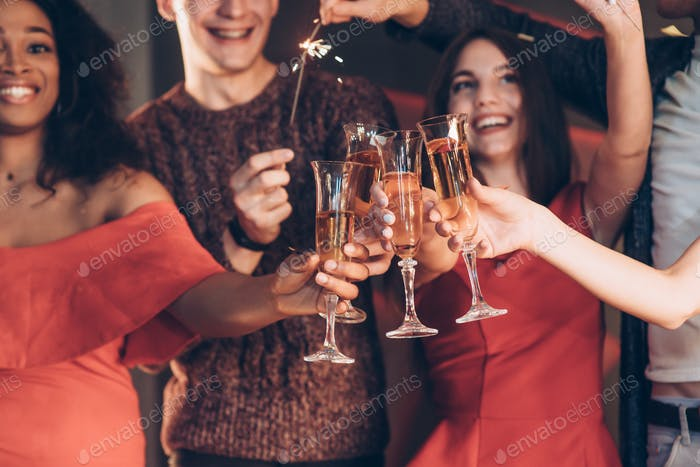 Multiracial friends celebrate new year and holding bengal lights and glasses with drink